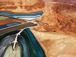 Aerial view of an arid, craggy landscape surrounding tailing ponds. Horizontal shot.