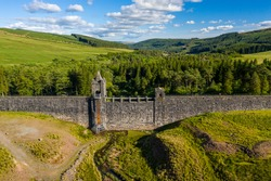 Aerial view of an empty reservoir with old dam wall (Upper Neuadd Reservoir, Brecon Beacons, Wales)