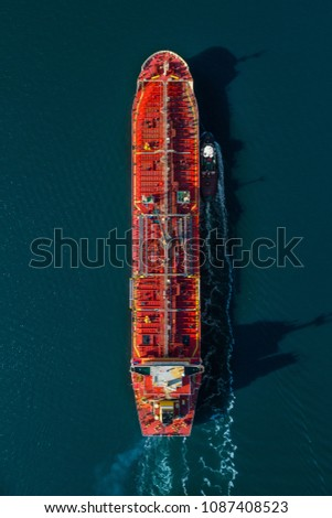 Aerial view of an oil tanker arriving at port assisted by a tug boat in New York harbor