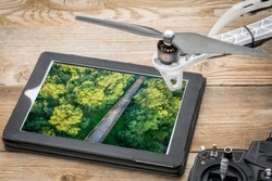Aerial view of an old bridge against green trees (Old Chain of Rocks Bridge over Mississippi RIver), reviewing image on a digital tablet