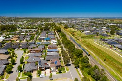 Aerial view of an outer suburb in Melbourne with train passing by
