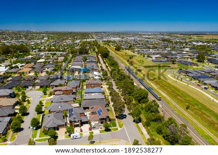 Aerial view of an outer suburb in Melbourne with train passing by ストックフォト ©