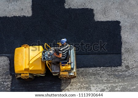 Aerial view of asphalting construction works with commercial repair equipment road parking for the car with yellow roller compactor machine. Contrast between new and old road surface #1113930644