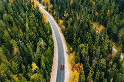 Aerial view of autumn color forest in the mountains and a road with red car in Finland Lapland.