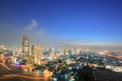Aerial view of Bangkok Skyline along Chaophraya River at dusk with star trail
