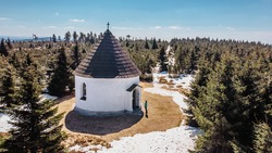 Aerial view of baroque Chapel of the Visitation of Virgin Mary,Kunstat Chapel,located in Eagle Mountains,Czech Republic.Circular floor plan,roof covered with shingles.Female traveler in late winter