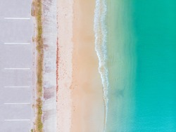 Aerial view of beach and blue sea with waves reaching shore along side with parking lot