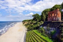 Aerial view of beautiful beach, sea and ruins of church in Trzesacz, Poland. Bright sunny day. Empty and closed due to covid 19 or coronavirus