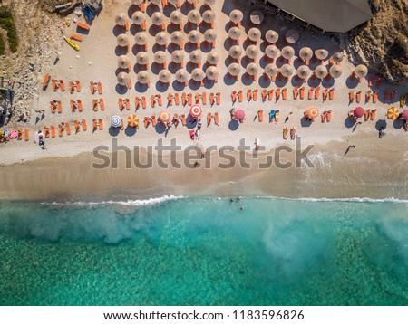 Aerial view of beautiful beach with orange sunbeds located in Saranda, Albania