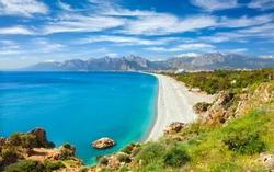 Aerial view of beautiful blue gulf and long Konyaalti beach in Antalya, Turkey. Antalya is Turkey's biggest international sea resort located on Turkish Riviera.