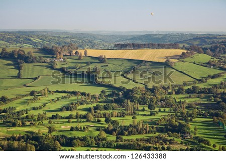 Aerial view of beautiful green countryside in Somerset, England. Includes fields, trees, golf course and a distant hot air balloon.