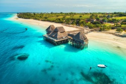 Aerial view of beautiful hotel in Indian ocean at sunset in summer. Zanzibar, Africa. Top view. Landscape with wooden hotel on the sea, azure water, sandy beach, green trees, boat. Luxury resort