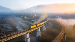 Aerial view of beautiful railway passenger train on a foggy sunrise on the old bridge over the river in mountain pass. Long blue train with yellow leaves, foggy river, sun rays, stone bridge. Top view