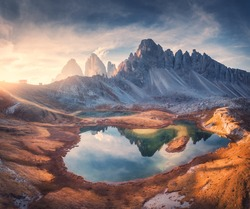 Aerial view of beautiful rocks, mountain lake, reflection in water and houses on the hill at sunset. Autumn landscape with mountains, blue sky and sunlight. Dolomites, Italy. Top view of Italian alps