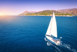 Aerial view of beautiful white sailboat in blue sea at bright sunny summer evening. Adriatic sea in Croatia. Landscape with yacht, mountains, transparent blue water, sky at sunset. Top view of boat