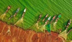 Aerial view of Ben Nom fishing village, a brilliant, fresh, green image of the green algae season on Tri An lake, with many traditional fishing boats anchored. Location in Dong Nai province, Vietnam