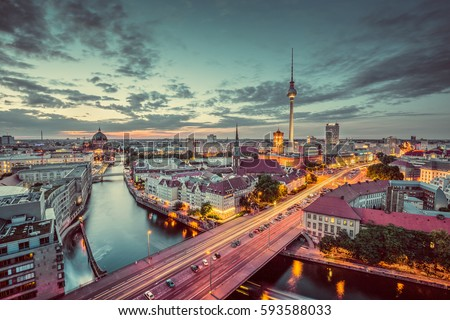 Aerial view of Berlin skyline with dramatic clouds in twilight during blue hour at dusk with pastel toned retro vintage filter effect, Germany