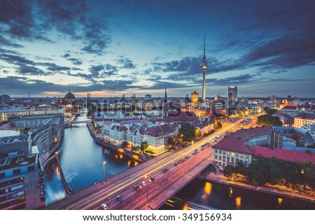 Aerial view of Berlin skyline with dramatic clouds in twilight during blue hour at dusk with retro vintage old Instagram style filter effect, Germany