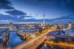 Aerial view of Berlin skyline with famous TV tower and Spree river in twilight during blue hour at dusk with dramatic clouds, Germany