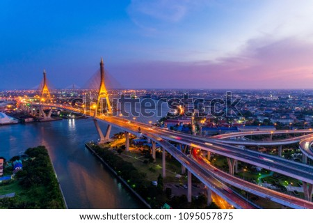 Aerial view of Bhumibol suspension bridge in Bangkok city with light trails of car on the road at sunset sky and clouds in Bangkok Thailand. #1095057875