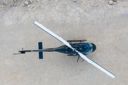 Aerial view of Black Helicopter on a desert ground