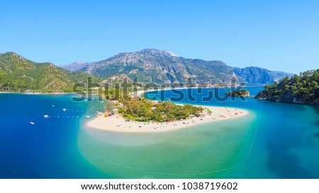 Aerial view of blue lagoon and pebble beach in Oludeniz, Fethiye district, Turquoise Coast of southwestern Turkey. Sunny summer day with clear blue sky in Oludeniz.