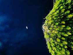 Aerial view of blue lake with a fishing boat and green forests with rocks on a summer day in Finland.