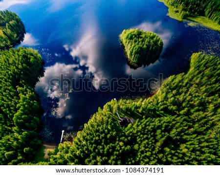 Aerial view of blue lake with island and green forests on a sunny summer day in Finland. Drone photography #1084374191