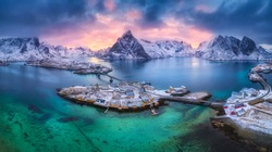 Aerial view of blue sea, snowy mountains, rocks, village, buildings, rorbu, road, bridge, colorful cloudy sky at sunset in winter.  Hamnoy in Lofoten islands, Norway. Panoramic landscape. Top view