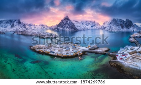Aerial view of blue sea, snowy mountains, rocks, village, buildings, rorbu, road, bridge, colorful cloudy sky at sunset in winter.  Hamnoy in Lofoten islands, Norway. Panoramic landscape. Top view Stockfoto ©