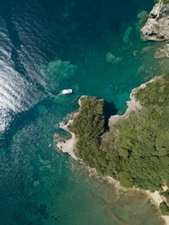 Aerial view of boat sailing near steep stone cliff with green forest above transparent emerald water of Adriatic sea. Stones on seabed. Unspoiled nature of Montenegro coast. Budva scenic landscape