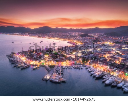 Aerial view of boats and beautiful city at night in Marmaris, Turkey. Amazing landscape with boats in marina bay, sea, city lights, mountains, red sky, clouds. Top view from drone.Harbor with yacht #1014492673