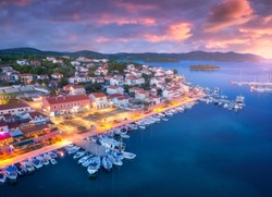 Aerial view of boats and yachts in port and city at night. Summer landscape with city lights, buildings, illuminated streets, mountain, motorboats, blue sea, colorful sky at sunset. Top view. Croatia