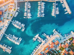 Aerial view of boats and yachts in port in old city at sunset. Summer landscape with houses with orange roofs, motorboats in harbor, clear blue sea, cars on the road. Beautiful architecture. Top view