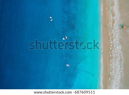 Aerial view of boats in mediterranean sea in Oludeniz,Turkey. Beautiful summer seascape with boats, clear azure water and sandy beach in sunny day. Top view of yachts from drone. Nature background