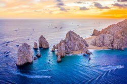 Aerial view of boats speeding by El Arco de Cabo San Lucas, Mexico at sunset, Baja California Sur