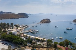 Aerial view of Bodrum's well-known holiday resort Gumusluk (Gümüşlük) bay and boats in the sea. TURKEY