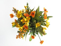 Aerial view of bouquet with wild flowers made of fabric in orange tones. Autumn flowers close up. Artificial colorful flower bouquet in warm and green tones. Colorful flower decoration.