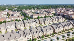 Aerial view of brand new two story condo and townhomes in downtown Flower Mound, Texas, America. Master-planned community and census-designated residential houses and apartment buildings