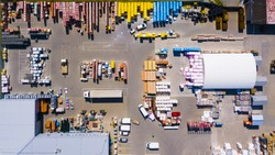 Aerial view of building materials warehouse. Large storage of construction materials in industrial city zone from above. Background texture concept.