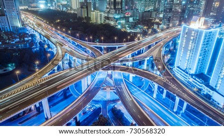 aerial view of buildings and highway interchange at night in Shanghai city #730568320