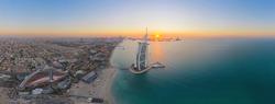 Aerial view of Burj Al Arab Jumeirah Island or boat building, Dubai Downtown skyline, United Arab Emirates or UAE. Financial district in urban city. Skyscrapers at sunset.