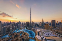 Aerial view of Burj Khalifa in Dubai Downtown skyline and fountain, United Arab Emirates or UAE. Financial district and business area in smart urban city. Skyscraper and high-rise buildings at sunset.