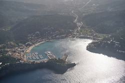 Aerial view of calm costal town located on verdant hilly shore washed by rippling azure sea on sunny weather