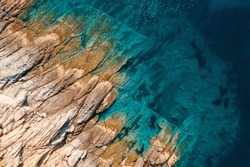 Aerial view of calm turquoise sea water and rocks from molten lava from drone. Pattern of sea surface and rocky shore. Thracian Sea, Greece. Rocky coast of the peninsula