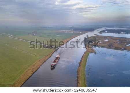 Aerial view of canal in Friesland with inland freight ships passing by. The Netherlands