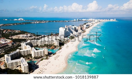 Aerial view of Cancun, Mexico showing luxury resorts and blue turquoise beach. showing people parasailing, swimming and tanning on the beach.