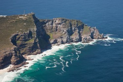 Aerial view of Cape point with lighthouse and Cape of Good Hope from a helicopter. Panorama of South Africa from birds eye view on a sunny day. Edge of the earth from helicopter view.