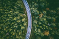 Aerial view of car driving through the forest on country road. Kaunas county, Lithuania
