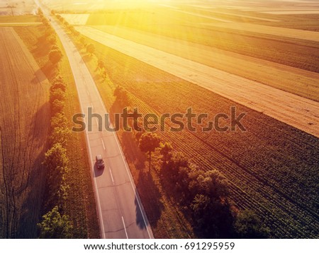 Aerial view of car traffic on two lane road through countryside and cultivated fields